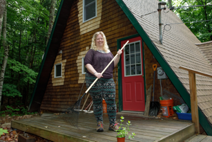 woman holding a rake standing in front of her home