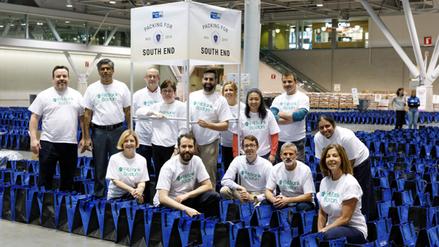 A group of 9 men and women wearing FHLBank Boston t-shirts standing behind a group of 5 squatting men and women who are wearing FHLBank Boston t-shirts with blue bags surrounding them