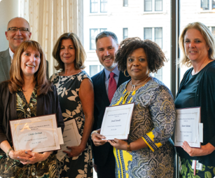 mix of three male employees and four female employees standing next to each other while holding award certificates
