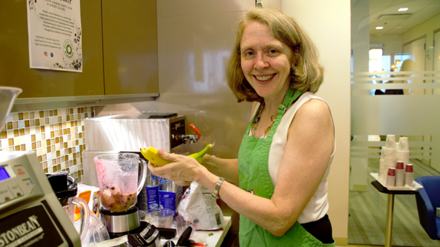 a smiling woman wearing a green apron holding a banana and standing in front of a partially filled blender