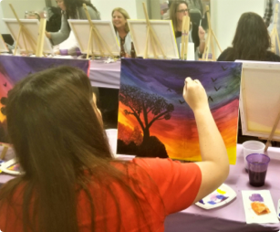 female employee seated while she is painting a colorful scene on a canvas